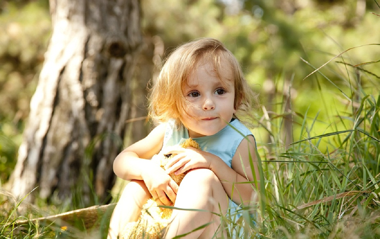 cute little girl hiding in a park