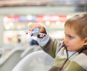 Boy-playing-with-toy-airplane-in-airport-web-1024x600