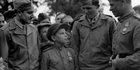 Sgt. S. Weinschenker and TSgt. William Topps talk to a 10-year-old boy who had been in uniform as an A/A loader for three years. (U.S. Air Force photo)