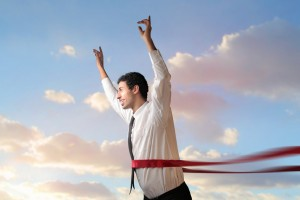 Triumphing businessman crossing the line