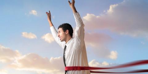 Triumphing businessman crossing the line