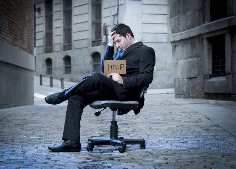 Business Man sitting on Office Chair on Street in stress