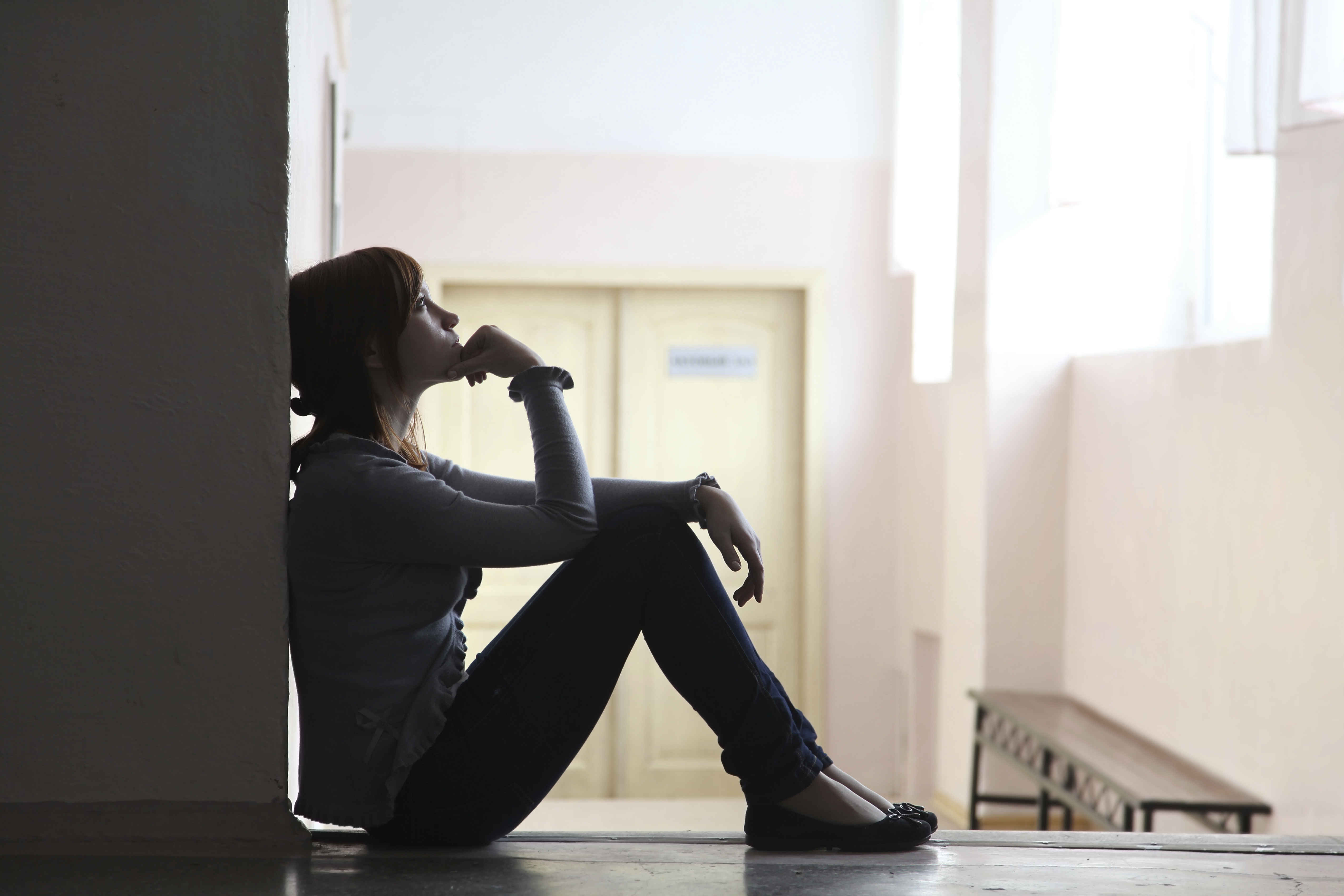 silhouette of a girl student sitting on the floor and thinking