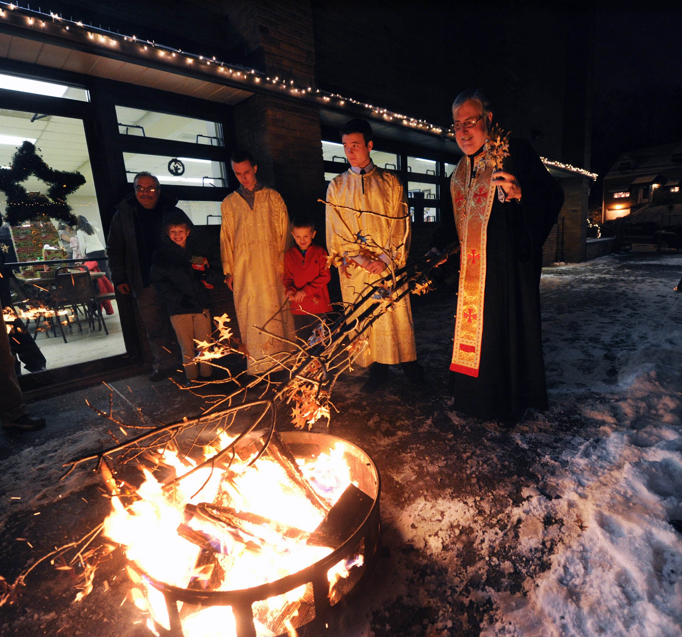"""John Heller / Post - Gazette Local / Yule Log McKeesport - Jan. 06, 2014 - Father Stevan Rocknage , right, Pastor of St. Sava Serbian Orthodox Church in McKeesport, oversees the burning of the """"Badnjak"""" or Yule log .The ceremony is usually held out doors but due to extreme cold weather, the Orthodox Christmas Eve service was held in the parish hall under the church. Only the burning of the log was outdoors."""