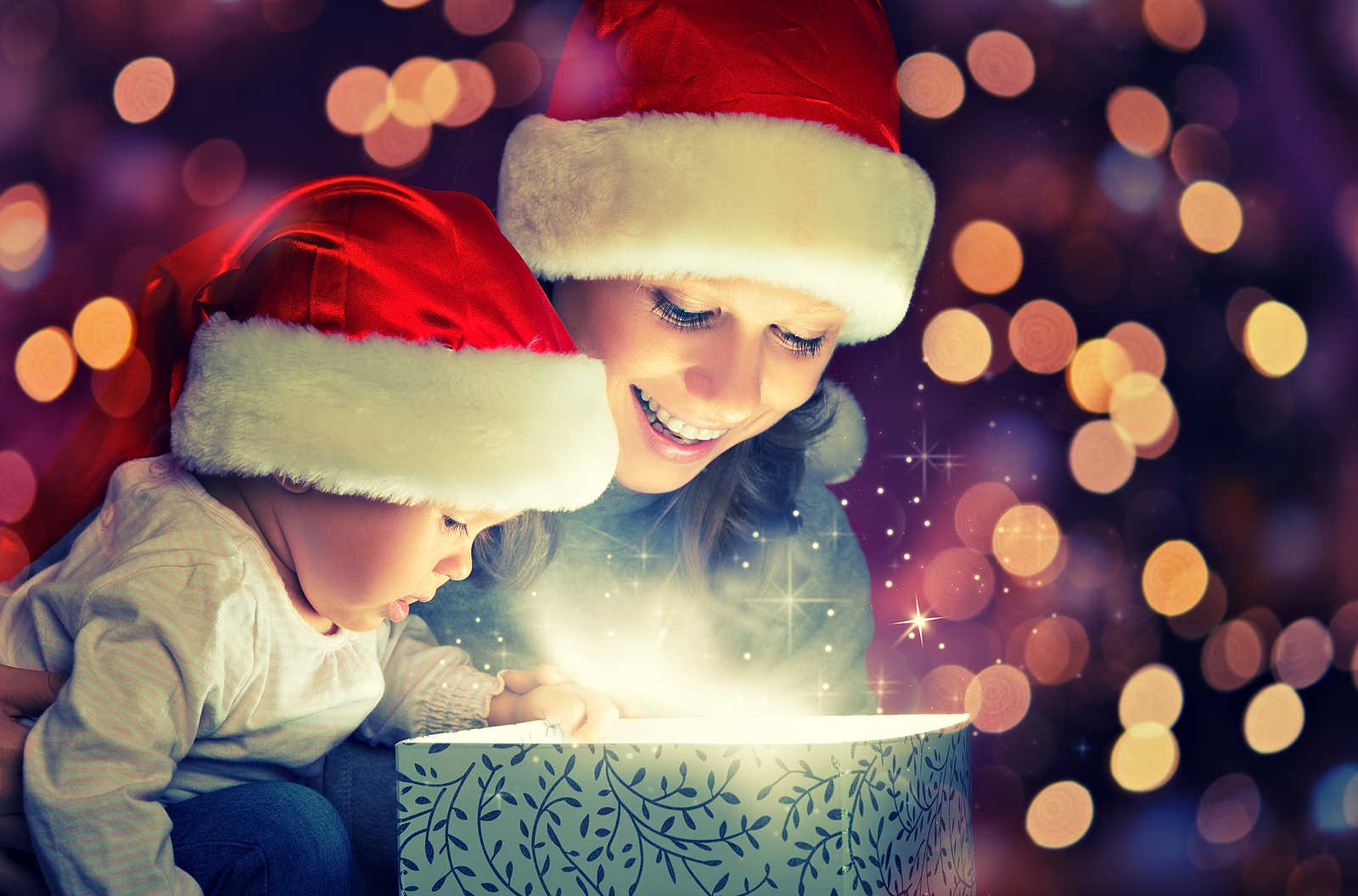 Bigstock-23346713-Christmas-Magic-Gift-Box-And-A-Happy-Family-Mother-And-Baby