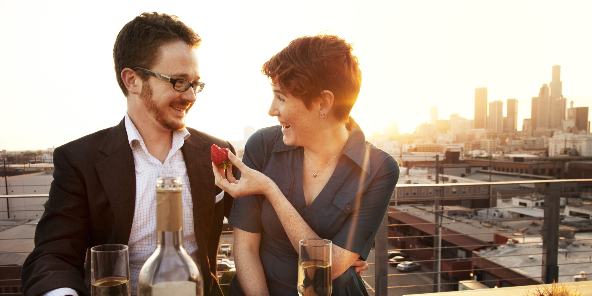 Couple on rooftop drinking wine