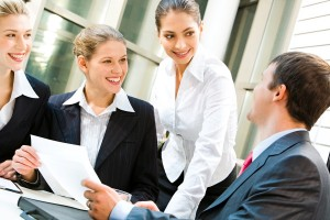 Image of three women looking at business man in a office