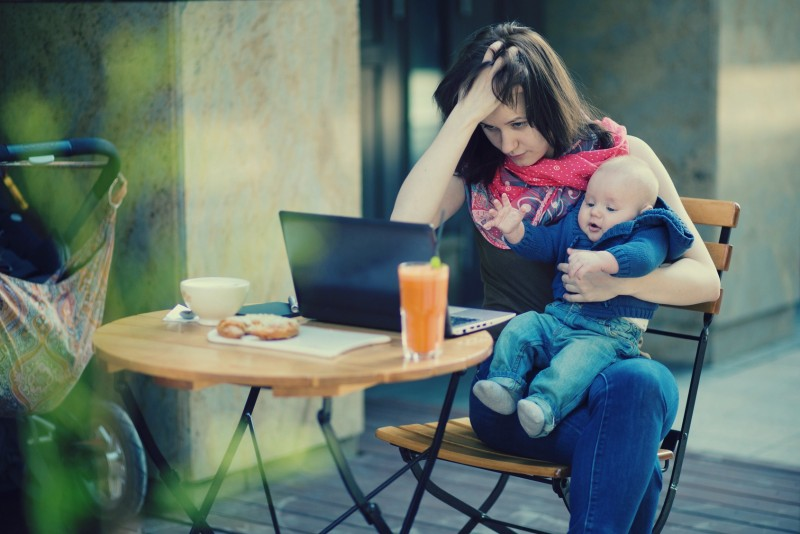 Tired young mother working oh her laptop and holding 4-month son