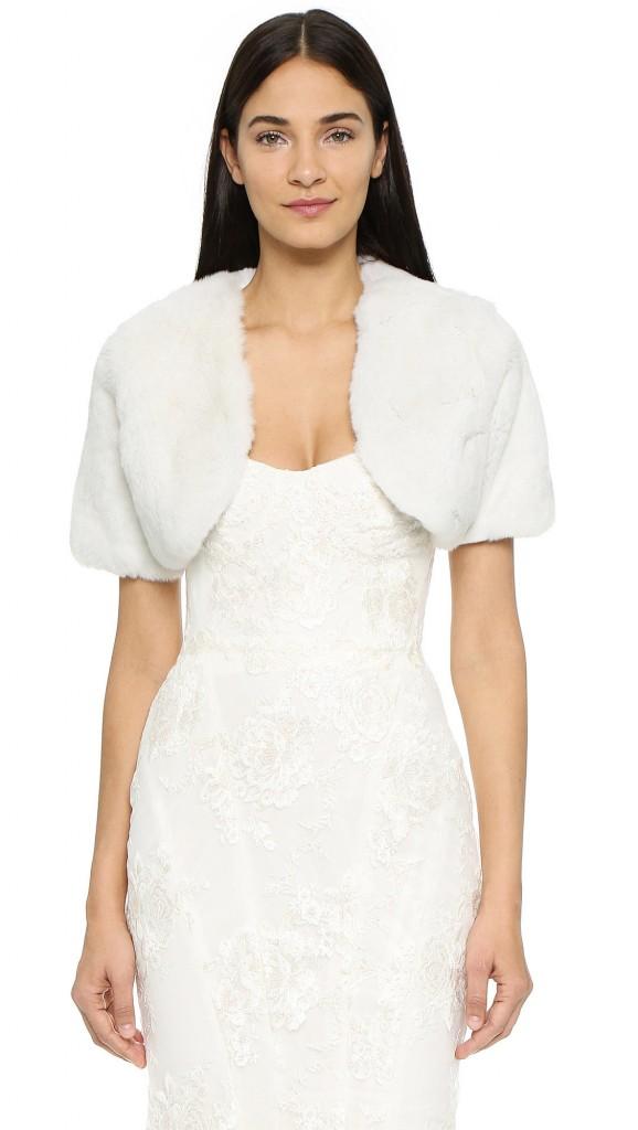 Женщина в свадебном платье и белом пушистом болеро