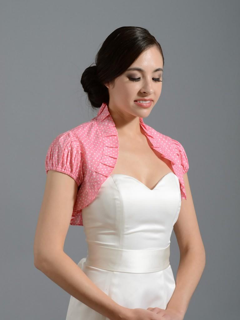 Женщина в белом атласном платье и розовом болеро в белый горошек