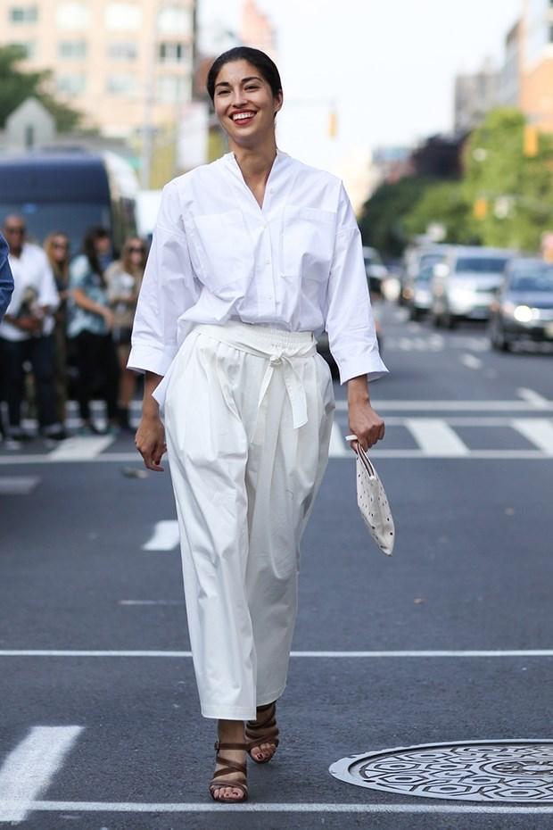 Женщина в белой свободной рубашке и белых свободных брюках