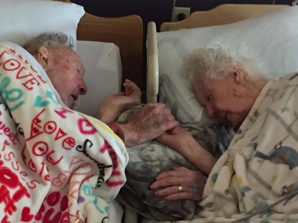 100-летний старик держит за руку свою 96-летнюю супругу незадолго до ее смерти