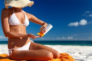 woman in white bikini applying sunblock at the beach
